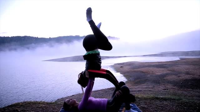 vídeos y material grabado en eventos de stock de acro yoga, dos personas deportivas práctica de yoga en pareja, pareja haciendo ejercicio que estira cerca del lago brumoso - pilates