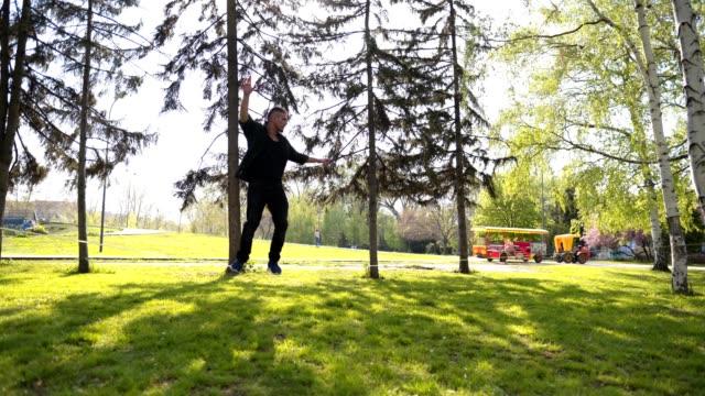 acrobat at a park balancing on a slackline - tightrope walking stock videos & royalty-free footage