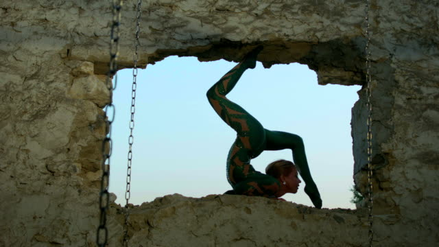 Acrobat exercising in ruined window frame
