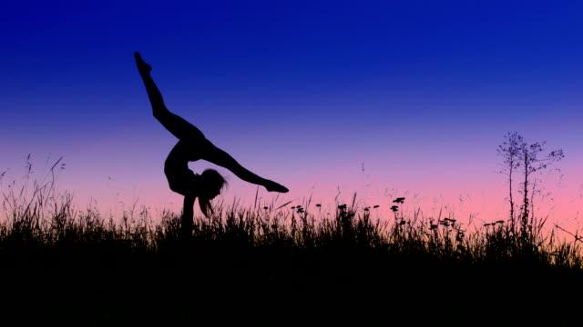 Acrobat ragazza esercitando nel campo posizione di freccia di sera