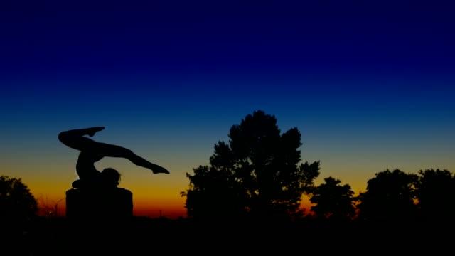Acrobat ragazza esercitando sulla colonna nella posizione di sera a freccia