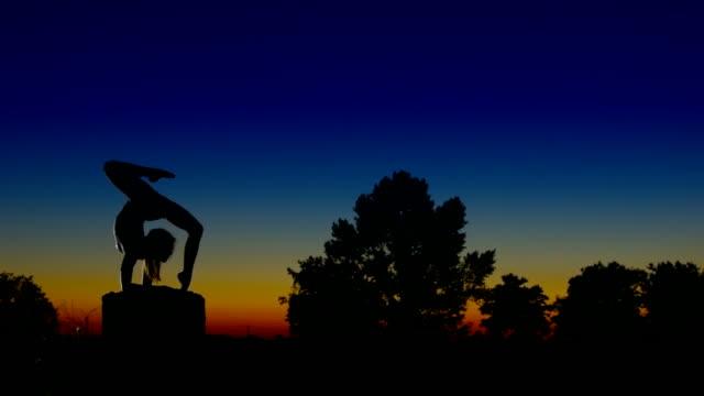 Acrobat girl exercising on column in the evening  Arrow position