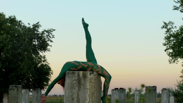 Acrobat lying at concrete column with leg rised up