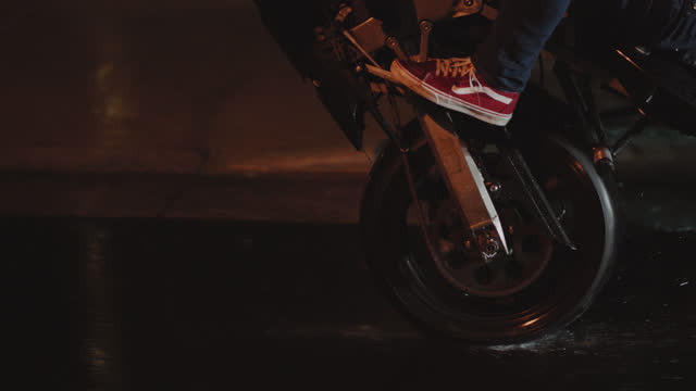 slo mo. acrobatic biker on stunt motorcycle kicks up water as he wheelies down rainy street at night. - customised stock videos & royalty-free footage