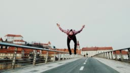 SLO MO Acrobatic breakdancer performing somersaults on the bridge