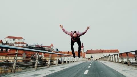 slo mo acrobatic breakdancer performing somersaults on the bridge - dancer stock videos & royalty-free footage