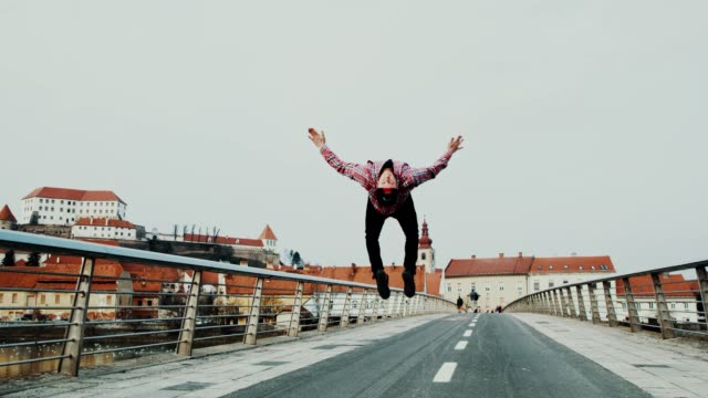 slo mo acrobatic breakdancer performing somersaults on the bridge - vita cittadina video stock e b–roll