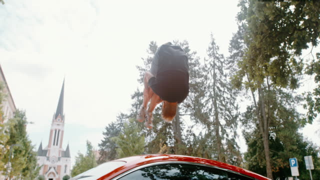 ms acrobatic teenage boy backflipping over parked red sports car - upside down stock videos & royalty-free footage