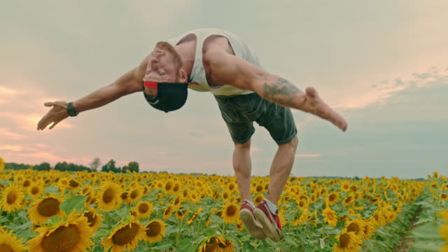 ms acrobatic young man backflipping in field of sunflowers - upside down stock videos & royalty-free footage