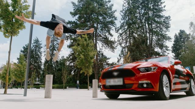 vídeos de stock e filmes b-roll de ms acrobatic young man backflipping in front of parked red sports car - malabarismo atividade desportiva