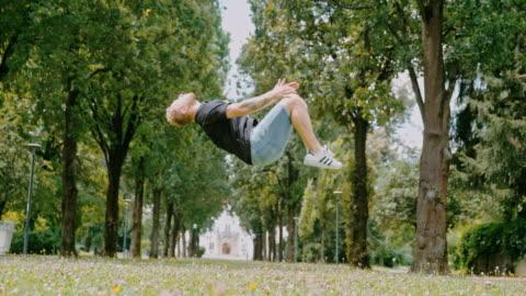 ms acrobatic ung man baklängesvolter i park - exalterande bildbanksvideor och videomaterial från bakom kulisserna