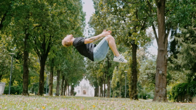 ms acrobatic young man backflipping in park - exhilaration stock videos & royalty-free footage