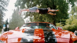 MS Acrobatic young man backflipping over red sports car