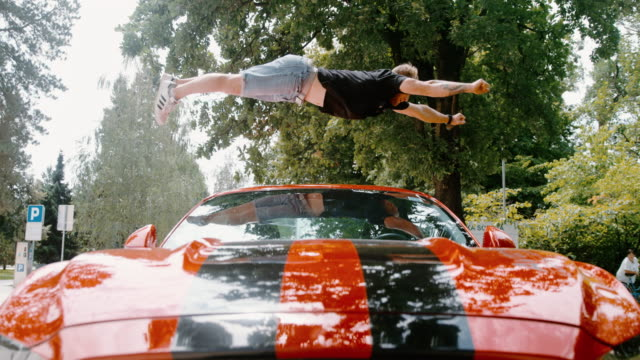 ms acrobatic young man backflipping over red sports car - super slow motion stock videos & royalty-free footage