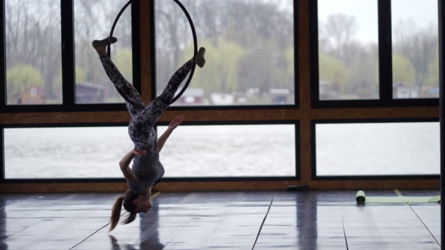 acrobatic young woman using aerial ring for stretching and exercising - ringmaster stock videos & royalty-free footage