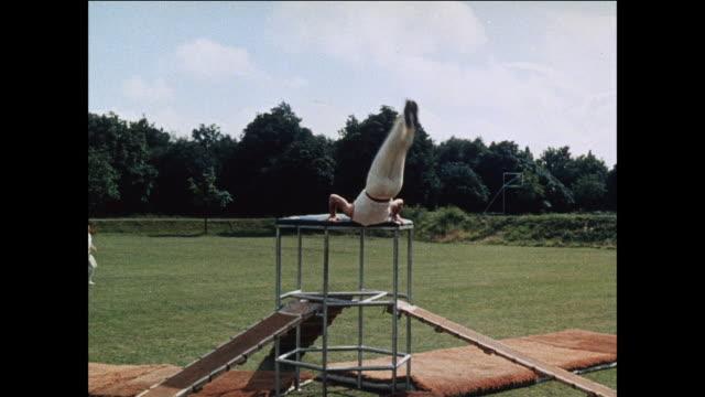 montage acrobats perform cross over jumps / uk - darstellender künstler stock-videos und b-roll-filmmaterial
