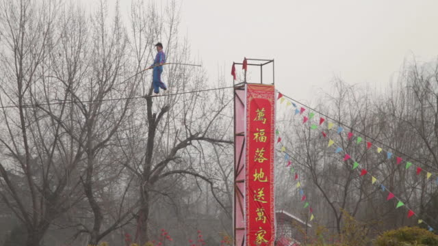 MS PAN ZO Acrobats performing high wire act during spring festival temple fair at small wild goose pagoda park AUDIO / xi'an, shaanxi, china