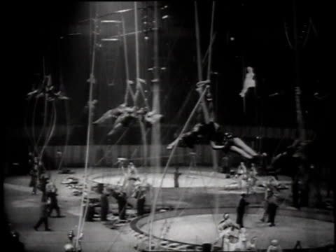 acrobats spinning from ropes without nets / female trapeze artist spinning on her head / audience watching / trapeze artist spins and resumes seated... - 1957 stock videos & royalty-free footage
