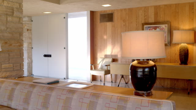 vídeos y material grabado en eventos de stock de ds across 1950s living room interior with custom-made extra long sofa,lamps and natural stone fireplace wall - palace room