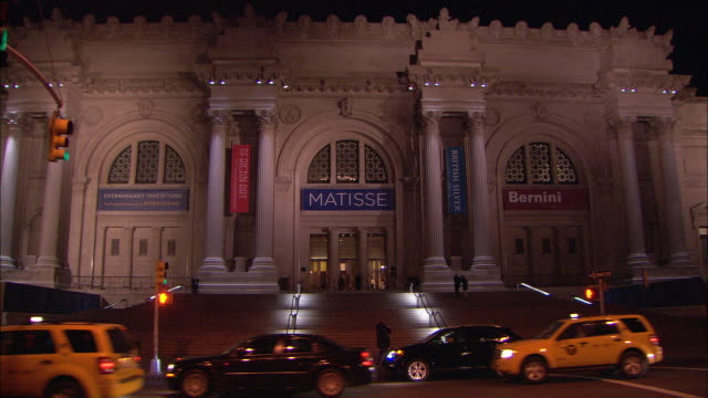 vídeos de stock, filmes e b-roll de across 5th avenue with traffic passing by in fg stairs entrance of the met featuring 'matisse' and 'bernini' banners - museu metropolitano de arte