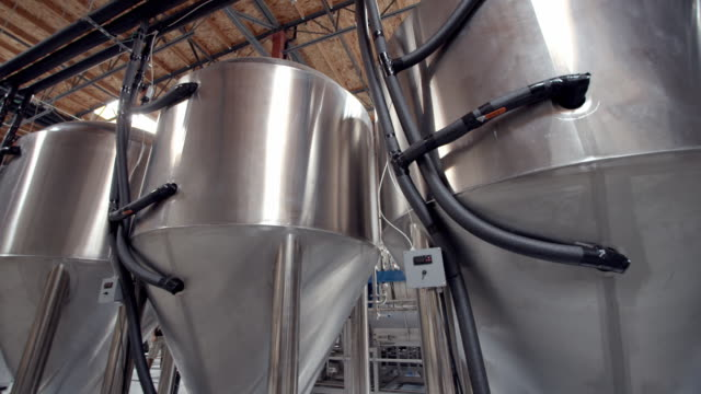 la ws pan across back side of stainless steel fermentation vessels connected by insulated hoses pumping propylene glycol anti freeze / thousand palms, california, usa - attrezzatura industriale video stock e b–roll