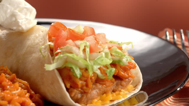 CU PAN across burrito on a plate with brown rice and beans as dollop of sour cream is spooned onto burrito