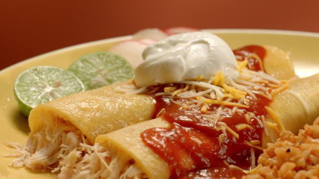 vídeos de stock e filmes b-roll de ecu pan across chicken enchilada dish with rice and black beans as dollop of sour scream is layered on top over enchiladas - modo de preparação de comida