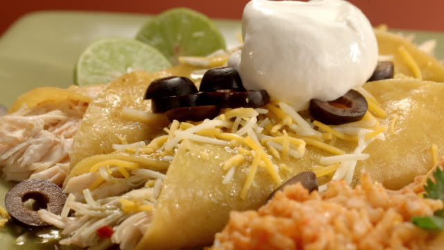 ecu pan across chicken enchiladas served with rice and beans as dollop of sour cream is dropped over enchiladas - sour cream stock videos & royalty-free footage