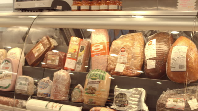 ds pan across delicatessen display case with hams, cheeses, salamis - milchprodukte stock-videos und b-roll-filmmaterial