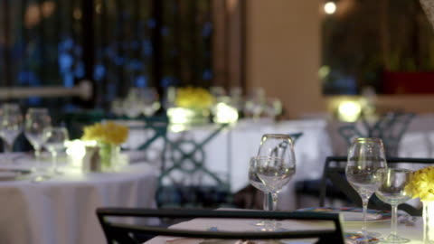 vídeos y material grabado en eventos de stock de pan across empty glasses and flowers on restaurant dining tables covered with white table cloths - ausencia