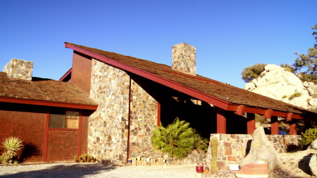 PAN across exterior mountain lodge home with natural stone walls and pitched roof covered with wood shingles