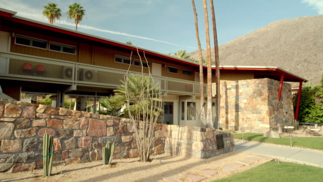 WS PAN across front of restored 1947 Del Marcos Hotel with long sloping roofline, native stone walls, redwood siding and asymmetrical design elements highlighting an organic architectural style