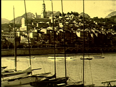 stockvideo's en b-roll-footage met across harbor, fishing boats, mediterranean, cote d'azur, mountains, seaside, alpes maritimes, french riviera. town of menton on january 01, 1920 in... - sepiakleurig