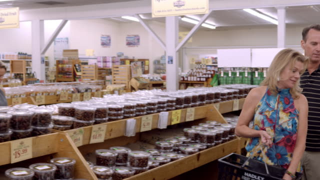 ws pan across health food store selling dried fruits and bagged nuts as customers browse shelves stocked with medjool dates / cabazon, california, usa - health food shop stock videos and b-roll footage