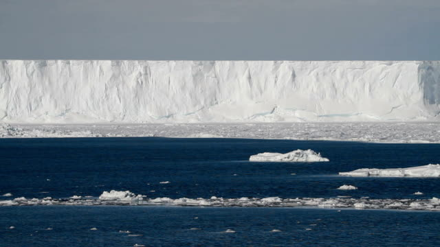 vídeos de stock, filmes e b-roll de pan across ice shelf with one floating iceberg, antarctica - antártica