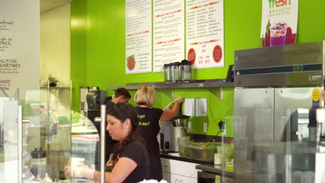 TD PAN across juice bar employees behind counter preparing organic and fresh juices and smoothies