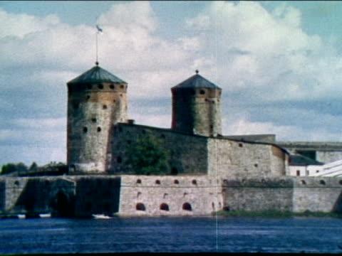 zo across lake of olavinlinna castle on nice cloudy day - castello video stock e b–roll