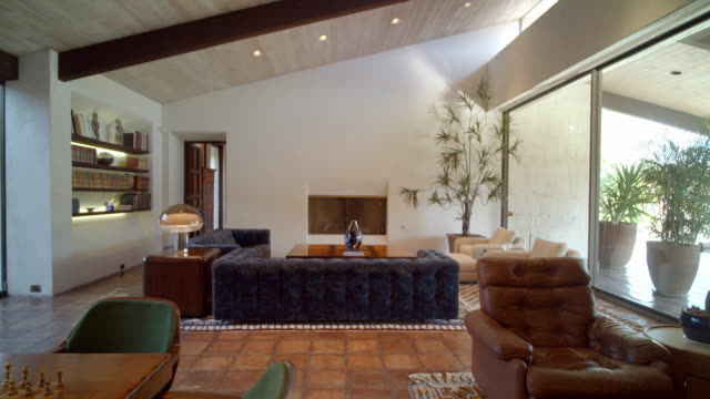 stockvideo's en b-roll-footage met ts across living room with 1971 original furniture in mid-century cody designed home with clay floor tiles, floor-to-ceiling glass windows and cathedral ceiling - huis interieur