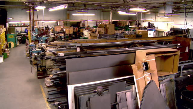 ws pan across metal working manufacturing plant with sheets of metal and oil drums and metal working machinery / redlands, california, usa - made in the usa kort fras bildbanksvideor och videomaterial från bakom kulisserna