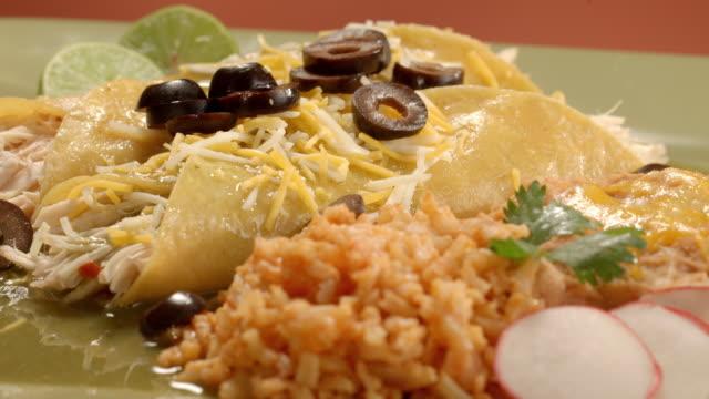 vídeos de stock e filmes b-roll de ecu pan across mexican dinner dish of chicken enchiladas served with rice as diced olives are added to the shredded cheese layer on top of the enchiladas - modo de preparação de comida