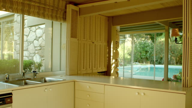 vídeos de stock e filmes b-roll de ds across mid-century modern kitchen with original cabinets and counter tops and louvered bifold shutters - portadas
