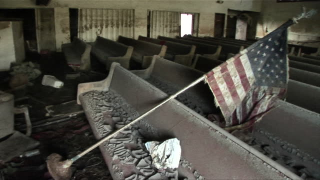 ms pan across mud-caked pews with dirty american flag laying across them in ninth ward church/ new orleans, louisiana - hurricane katrina stock videos and b-roll footage