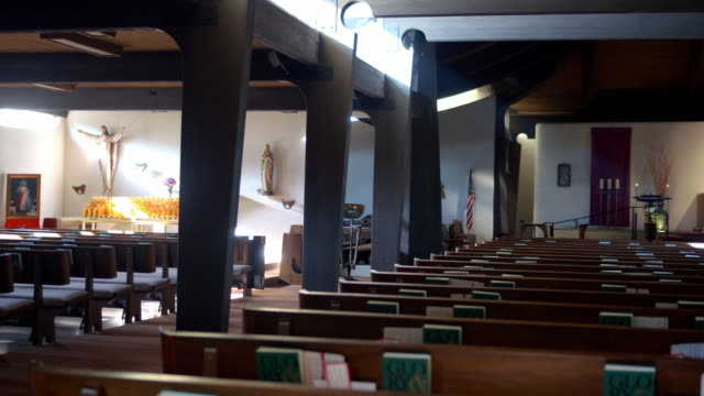 ts pan across pews in modern catholic church as overhead lights are switched on - church stock videos & royalty-free footage