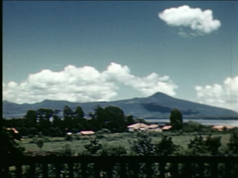 vidéos et rushes de pan across rooftops with mountains in background / pan across countryside with lake and mountains / mexican indians wearing sombreros and sarapes... - châle