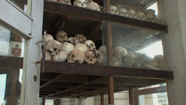 ws tu across  shelves in stupa loaded with skulls, choeung ek, cambodia - mass grave stock videos and b-roll footage