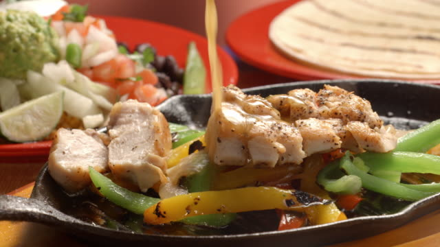 CU PAN across sizzling fajita pan with chicken and bell peppers as sauce is poured over sliced pieces of chicken breast