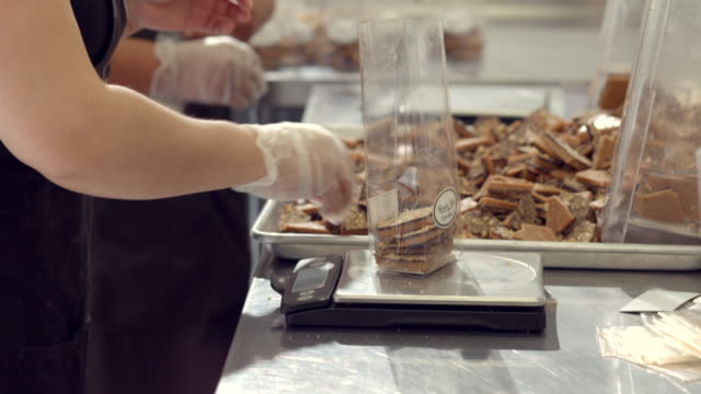cu pan across small cellophane bags filled with almond toffee bark as workers fill bags and put bags on scale to verify weight / rancho mirage, california, usa - cellophane stock videos and b-roll footage