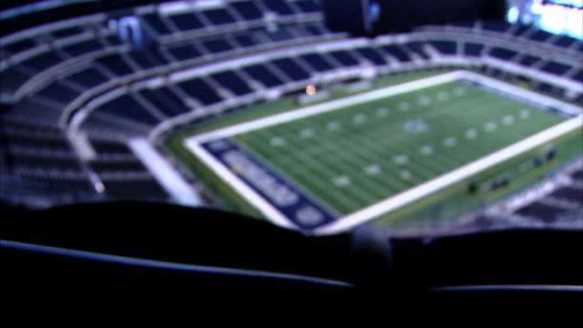 across soft football field in empty stadium filled w/ blue seats, partial high definition monitor visible over field. sports, venue, event, dallas,... - large scale screen stock videos & royalty-free footage