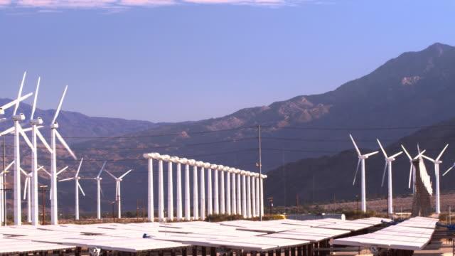 PAN across solar photovoltaic power plant near wind farm and freeway traffic  / Palm Springs, California, USA