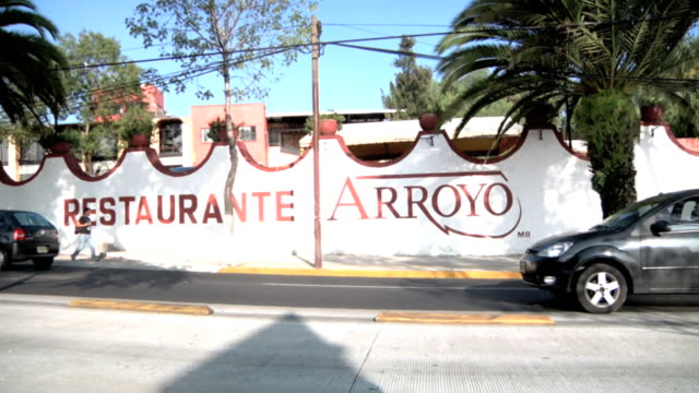 red letterings on restaurant wall side restaurante arroyo, traffic, vehicles driving through frame fg, unidentifiable male across street walking.... - restaurante stock videos & royalty-free footage
